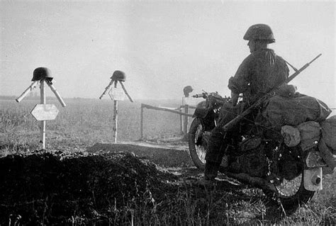 WWII --- German soldier on motorcycle at the graves of